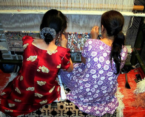 Mother and daughter working together on a rug in Uzbekistan.